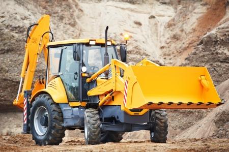 backhoe loader: Wheel excavator loader with risen bucket at eathmoving works in construction site or sandpit