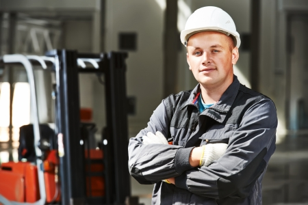 front loader: conductor joven trabajador del almacén sonriente en uniforme delante de la carretilla elevadora apiladora loader