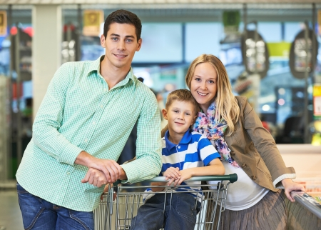 shopping man: Family shopping. Young man and woman with child during shopping at supermarket store
