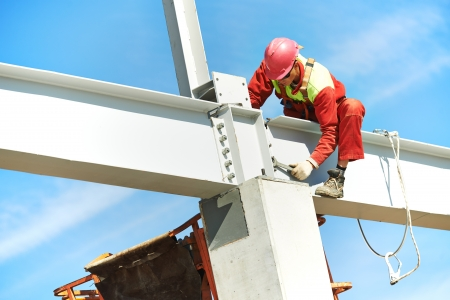 assembling: worker in uniform and safety protective equipment at metal construction frames installation and assemblage