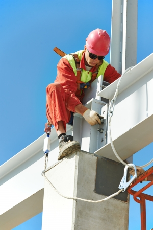 construction workers: worker in uniform and safety protective equipment at metal construction frames installation and assemblage