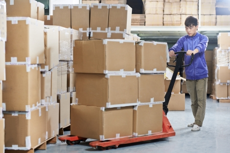 Male chinese worker with fork pallet truck stacker in warehouse loading group of boxes packages photo