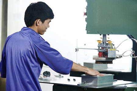 punch press: chinese worker operating press in china production factory manufacturing Stock Photo
