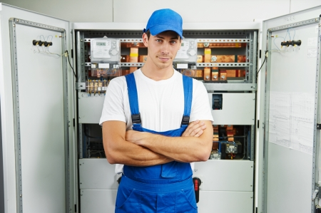 Young adult electrician builder engineer in front of equipment in distribution fuse box Imagens