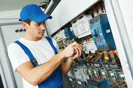 electricista: Los j�venes adultos de electricista constructor ingeniero atornillar equipo en la caja de fusibles