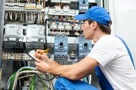 electricista: Ingeniero constructor electricista adulto joven que revisa el equipo contador eléctrico en la caja de fusibles de distribución