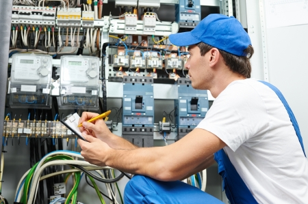 electric wire: Young adult electrician builder engineer inspecting electric counter equipment in distribution fuse box