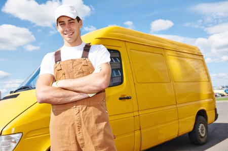 parcels: Smiling young male delivery courier man in front of cargo van for delivering or relocation