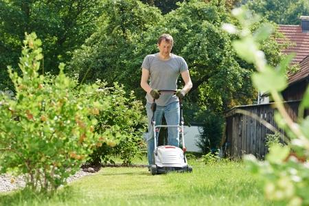 cut grass: man cutting grass in his garden yard with lawn mower