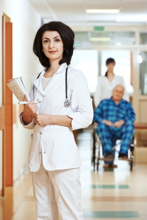 Portrait of smiling doctor in medic uniform in hospital clinic hallway photo