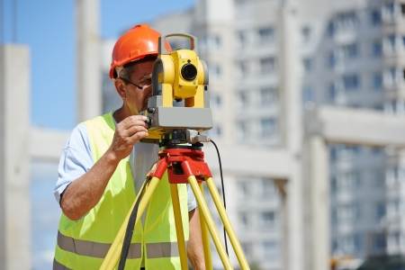 roadwork: builder worker with theodolite transit equipment at construction site outdoors during surveyor work Stock Photo