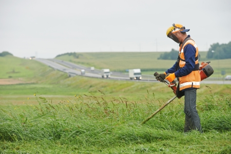 lawn mower worker man cutting grass in green field photo