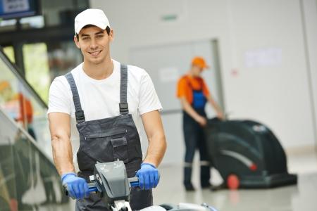 유니폼 걸레 청소기 남성 근로자는 복도 패스 또는 비즈니스 건물의 복도 바닥 청소 스톡 콘텐츠