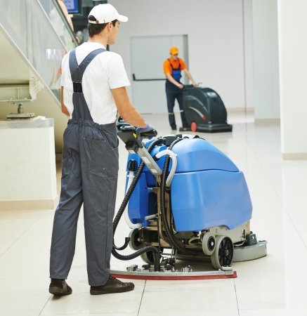 Cleaner male man workers with mop in uniform cleaning corridor pass or hall floor of business building photo