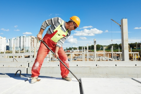 ceiling slab: builder worker with metal crow bar installing concrete floor slab panel at building construction site Stock Photo