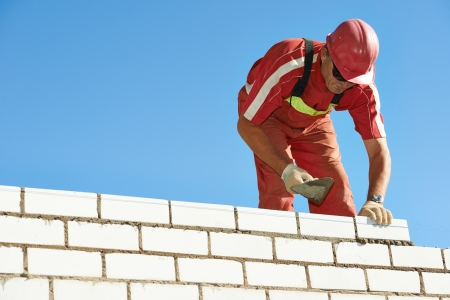 Builder construction mason worker bricklayer installing red brick with trowel putty knife outdoors Stock Photo