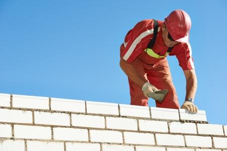 Constructor de la construcción albañil albañil trabajador de la instalación de ladrillo rojo con llana masilla cuchillo al aire libre Foto de archivo - 21766386