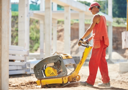 compacting: builder worker compacting soil with vibration plate compaction machine during pavement roadwork