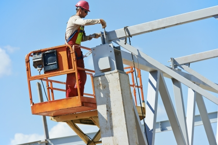 assemblage: worker joiner in uniform and safety protective equipment at metal construction frames installation and assemblage