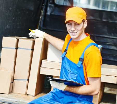 young male postal delivery courier man in front of cargo van delivering package photo