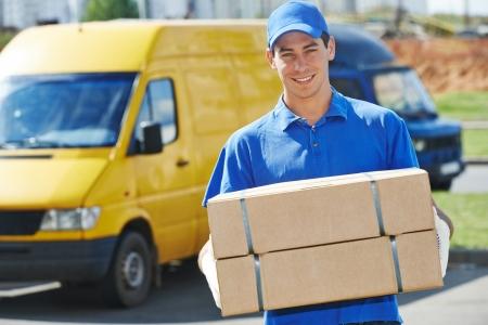 Giovane uomo maschio sorridente del corriere di consegna postale davanti al furgone del carico che consegna pacchetto