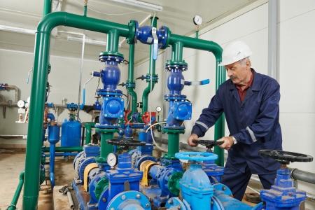 bomba de agua: ingeniero técnico de ingeniería de sistemas contra incendios o un sistema de calefacción de abrir la válvula de equipos en una sala de calderas