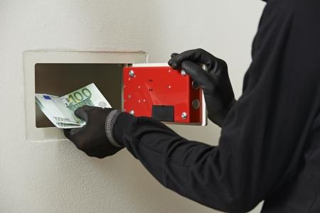 Thief burglar stealing euro money during home safe codebreaking photo