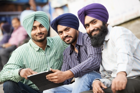 Group portrait of smiling authentic native indian punjabi sikh men in turban with bushy beard photo