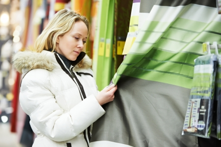 shopping mall: woman choosing curtain in home interior decoration shopping mall supermarket