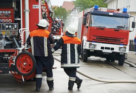 voiture de pompiers: Pompier dans le moteur de feu d'exploitation uniforme ou camion de pompiers en service pendant la formation
