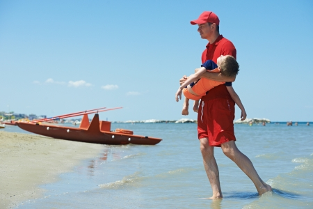 Lifeguard man with rescued child from drowning on a sea beach 스톡 콘텐츠