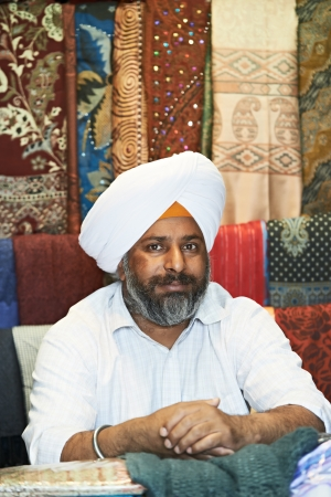 Portrait of Indian sikh man seller in turban with bushy beard at shawl shop photo