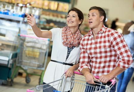 Family couple with trolley cart in meat grocery supermarket during weekly food shopping photo