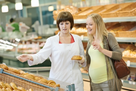 Sales assistant in supermarket demonstrating food to female customer during shopping at store photo