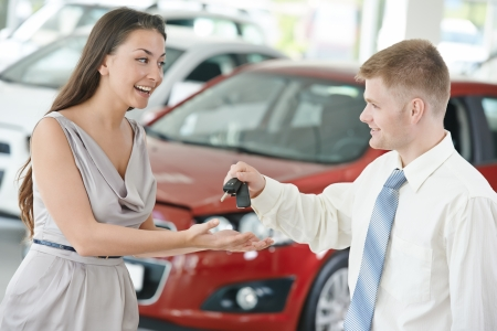 car dealers: salesperson demonstrating new automobile car to young woman