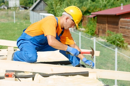 restoring: construction carpenter worker nailing wood board with hammer on roof installation work Stock Photo