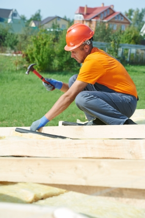 trussing: construction carpenter worker nailing wood board with hammer on roof installation work Stock Photo