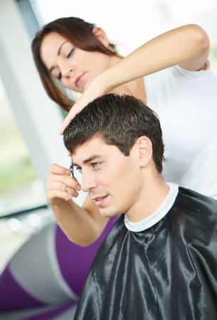 Woman hairdresser cutting hair of young man client at beauty parlour photo