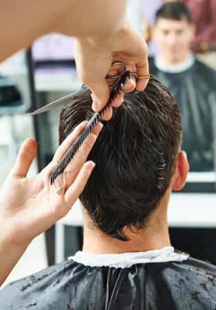 Peluquería hace corte de pelo de hombre joven en salón de belleza Foto de archivo