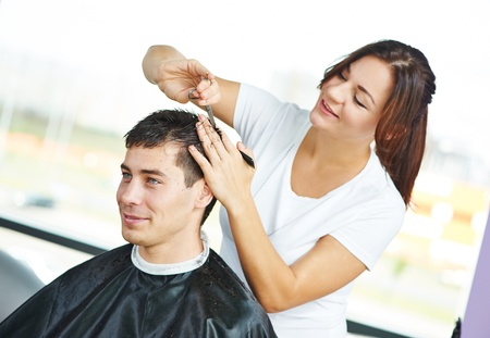 haircutter: Female hairdresser cutting hair of smiling man client at beauty parlour
