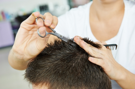 Hairdresser making haircut to young man at beauty parlour photo
