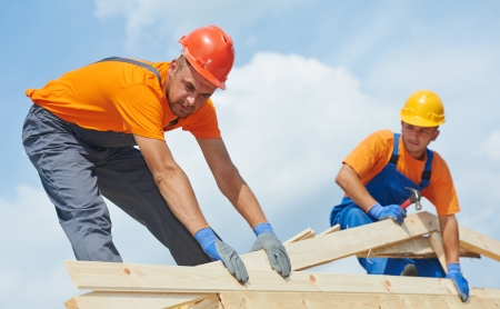 Two construction roofer carpenter worker installing wood board roof Stock Photo