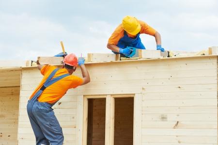trussing: Due carpentieri edili conciatetti operai di installare scheda di legno del tetto