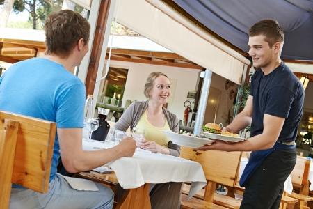 restaurante italiano: porci�n del camarero joven pareja en un peque�o restaurante italiano