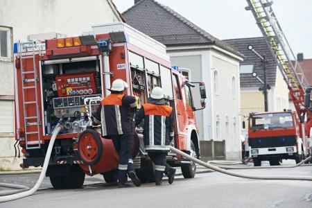 voiture de pompiers: Deux pompiers dans le moteur de fonctionnement uniforme ou camion de pompiers en service au cours de la formation