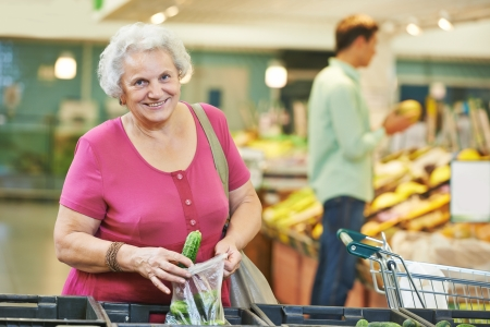 senior eating: woman during shopping at fruit or vegetable supermarket store shop