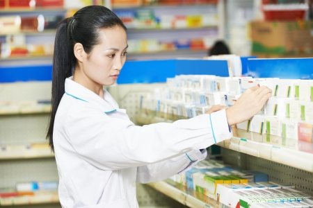 drug store: chinese pharmacist chemist woman choosing tablets in china pharmacy drugstore