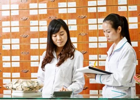 Two cheerful chinese pharmacist chemist woman standing in china pharmacy drugstore Imagens - 21945905