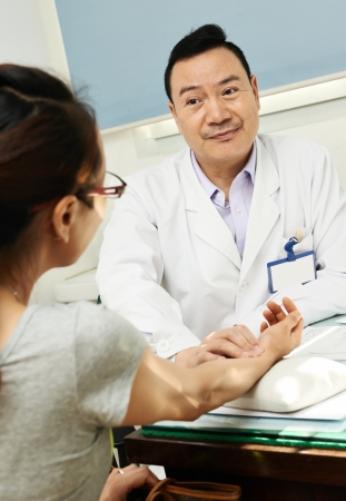 Chinese adult asian male doctor in clinic during pulse diagnosis photo