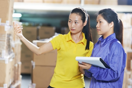 two young chinese female workers in uniform in discussing warehousing system Stock Photo - 21945943